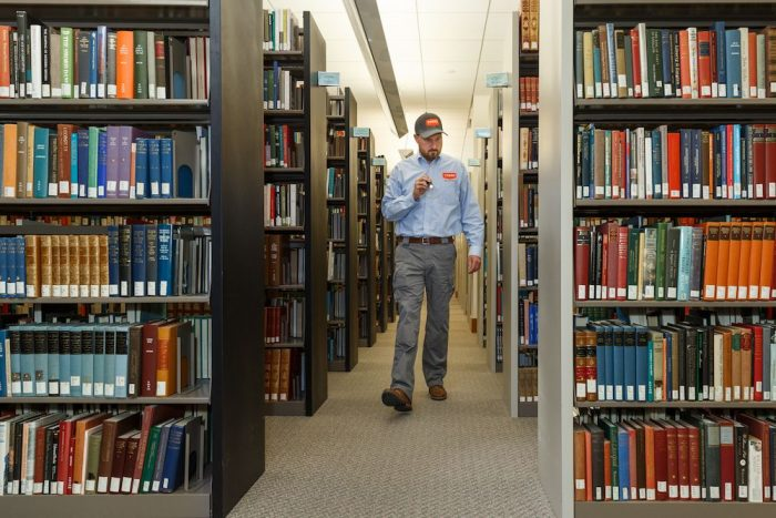 Thorn professional inspecting for pests in a library