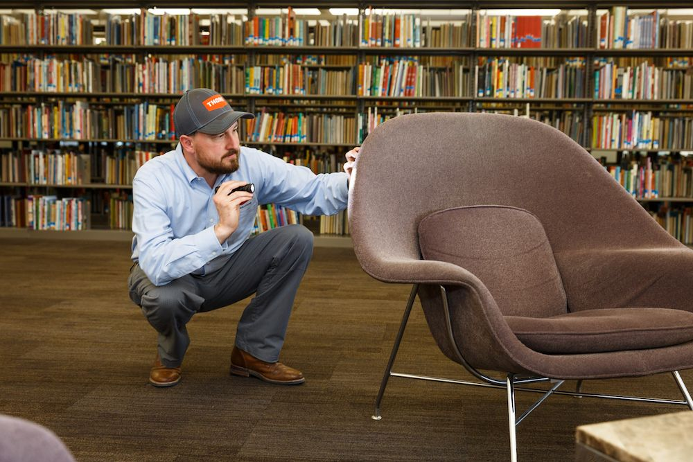 Thorn professional inspecting for pests in a library seating area